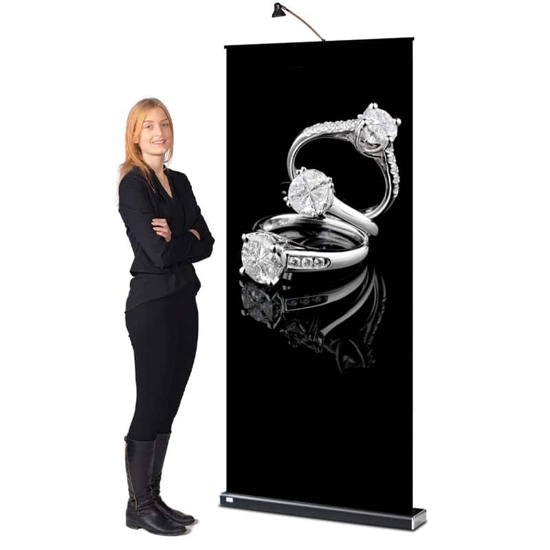 model beside standing m2 banner stand display with black hardware and light