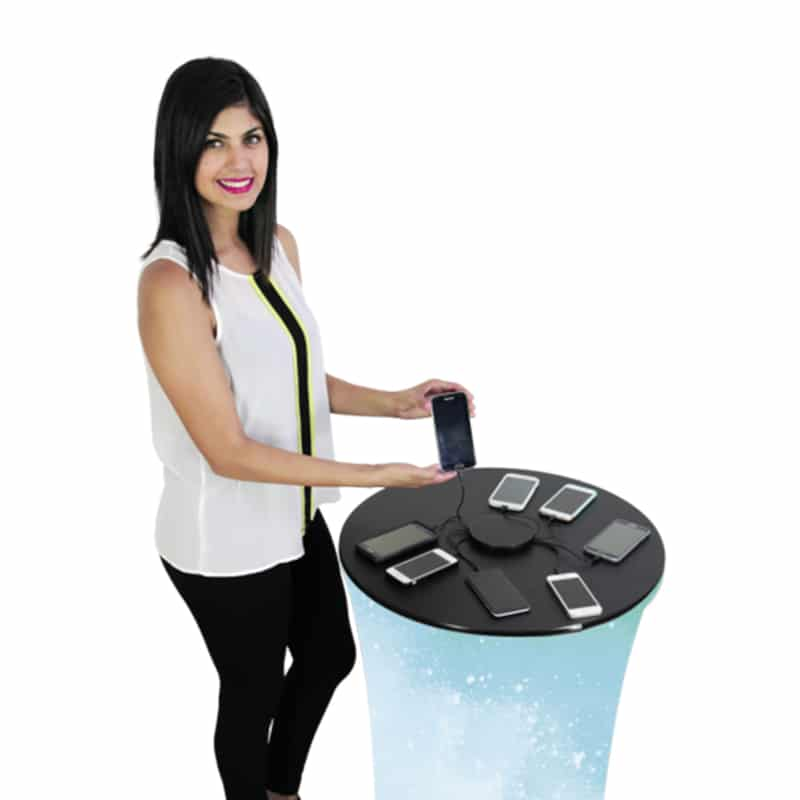 model standing at formulate round charging counter showing cell phones connected