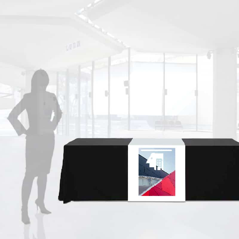 fabric table runner draped over table front to back with full-color logo and woman silhouette for scale